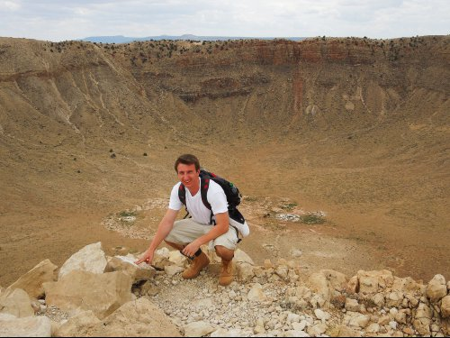NASA Goddard intern Sebastian Fischer crouches in front of Meteor Crater.